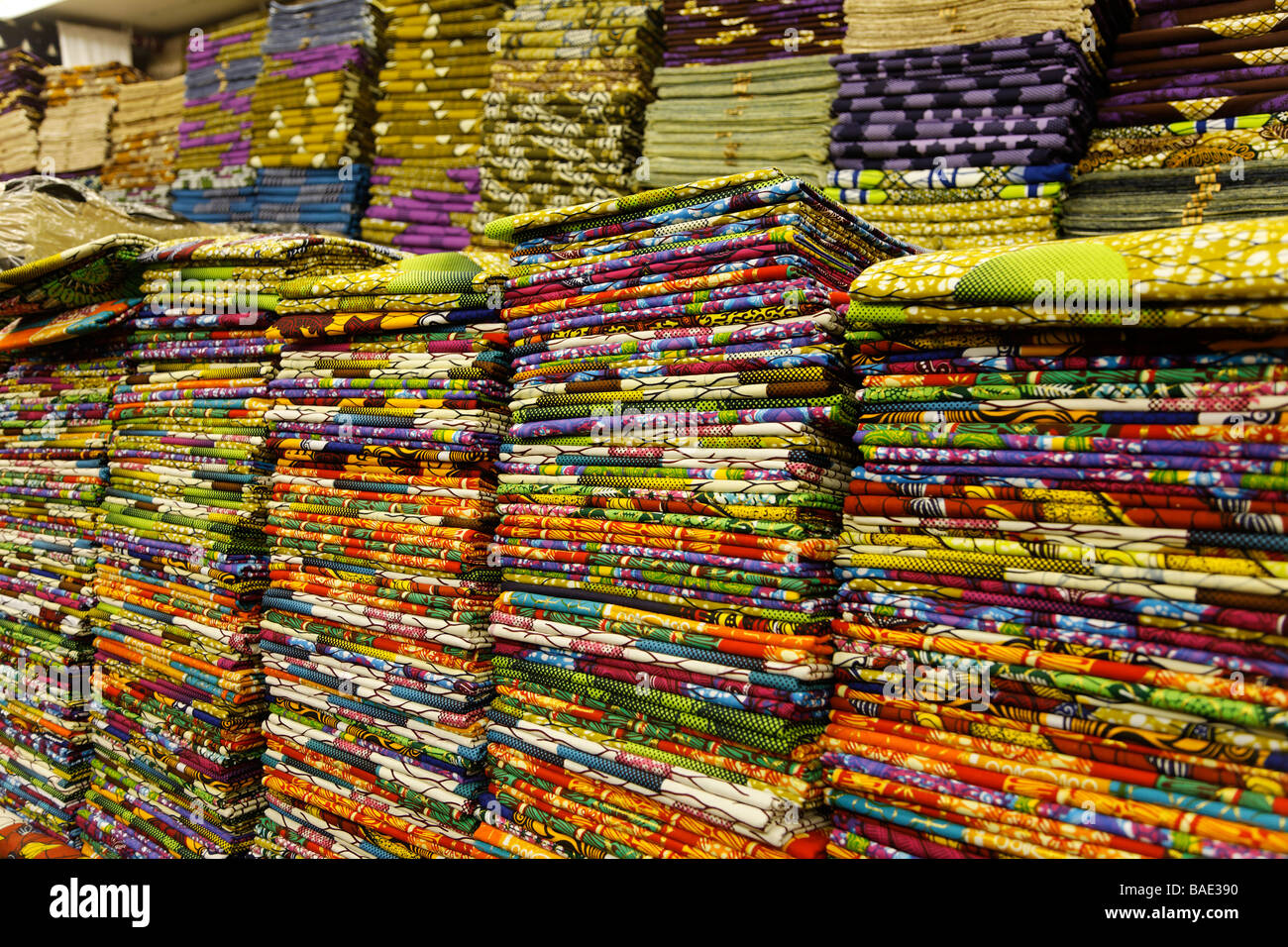 African textiles fabric piled in shop - Stock Image