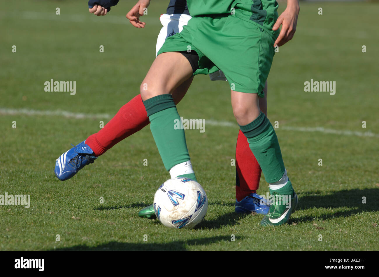 Detail of two footballers legs and feet with football. - Stock Image