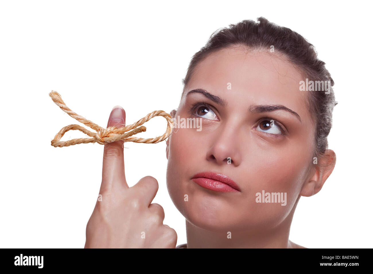 Young woman trying to remember what the piece of string round her finger was meant to remind her of isolated white - Stock Image