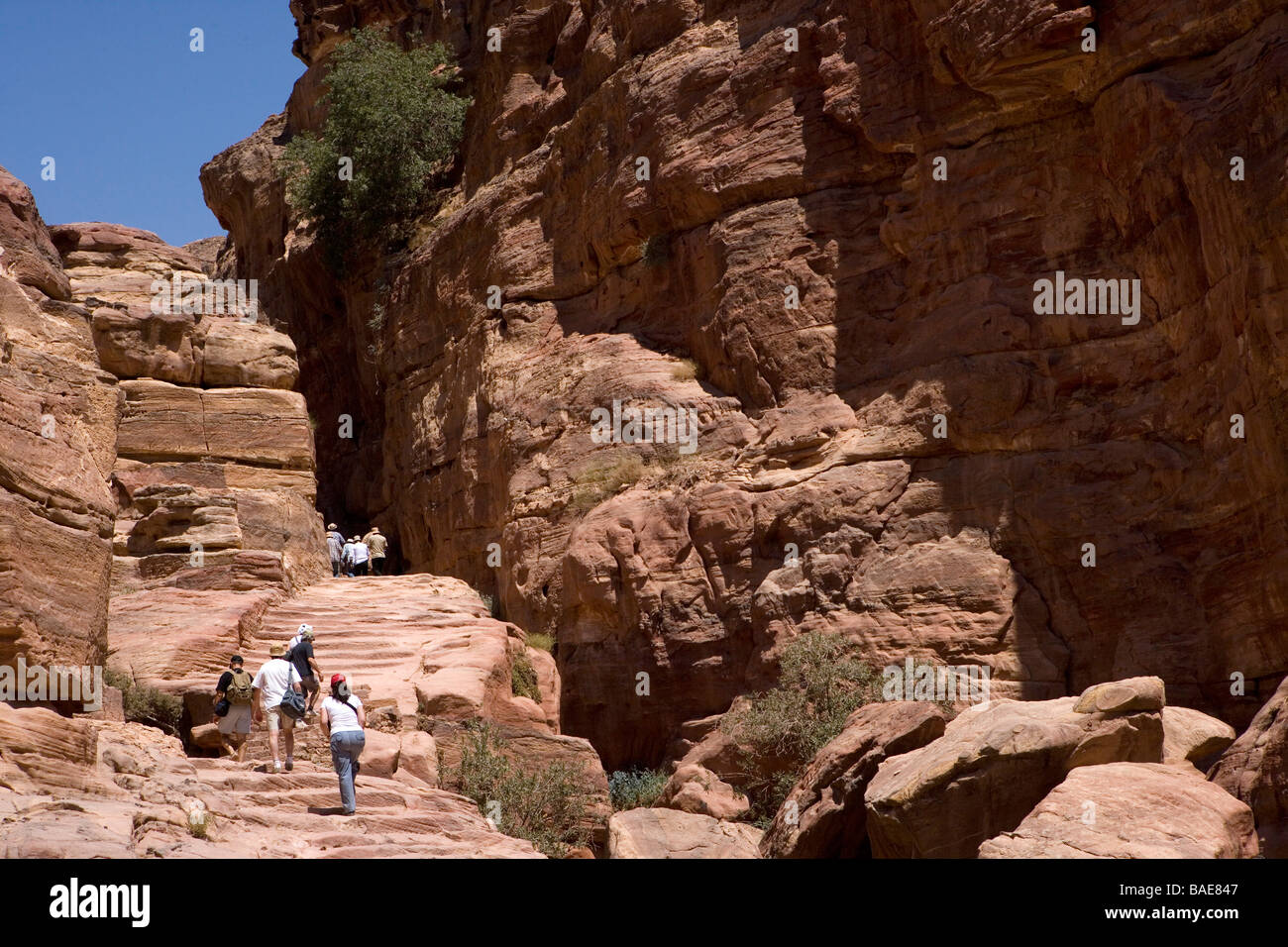 Tourist hike up the steep track on Jabal Al-Deir on their way to visit the Monastery in the ancient city of Petra, Stock Photo