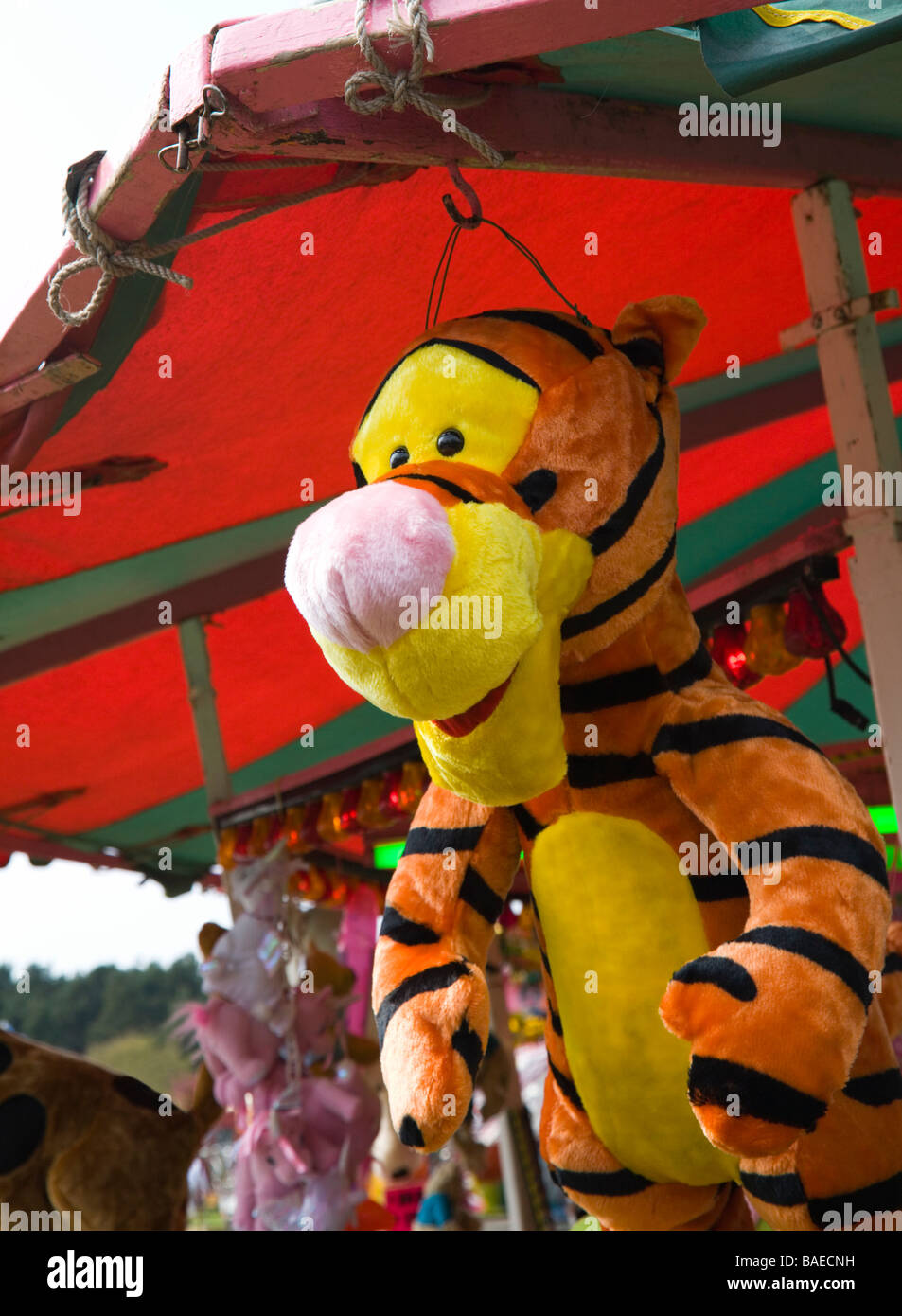 Disney 'Tigger'. A stuffed cuddly toy tiger, offered as a prize, hanging from a stall at a fairground. UK. - Stock Image
