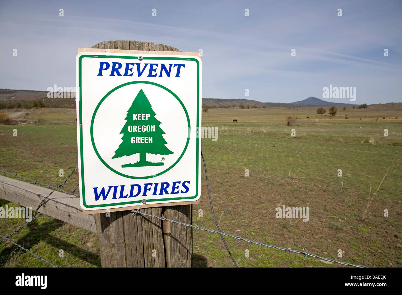 A Prevent Wildfires sign on a fencepost says Keep Oregon Green - Stock Image