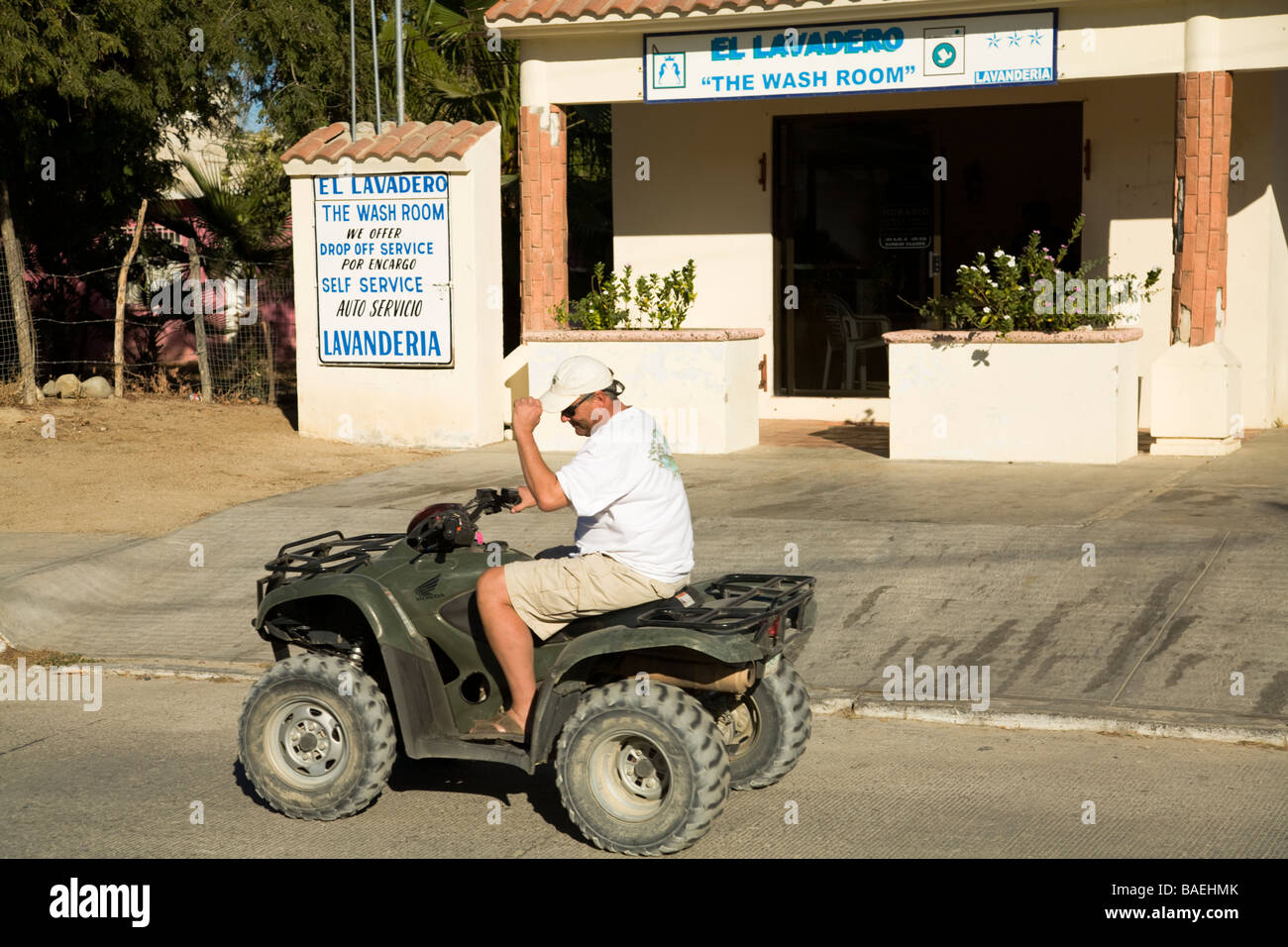 MEXICO Los Barriles Retired American man driving ATV on street in town - Stock Image