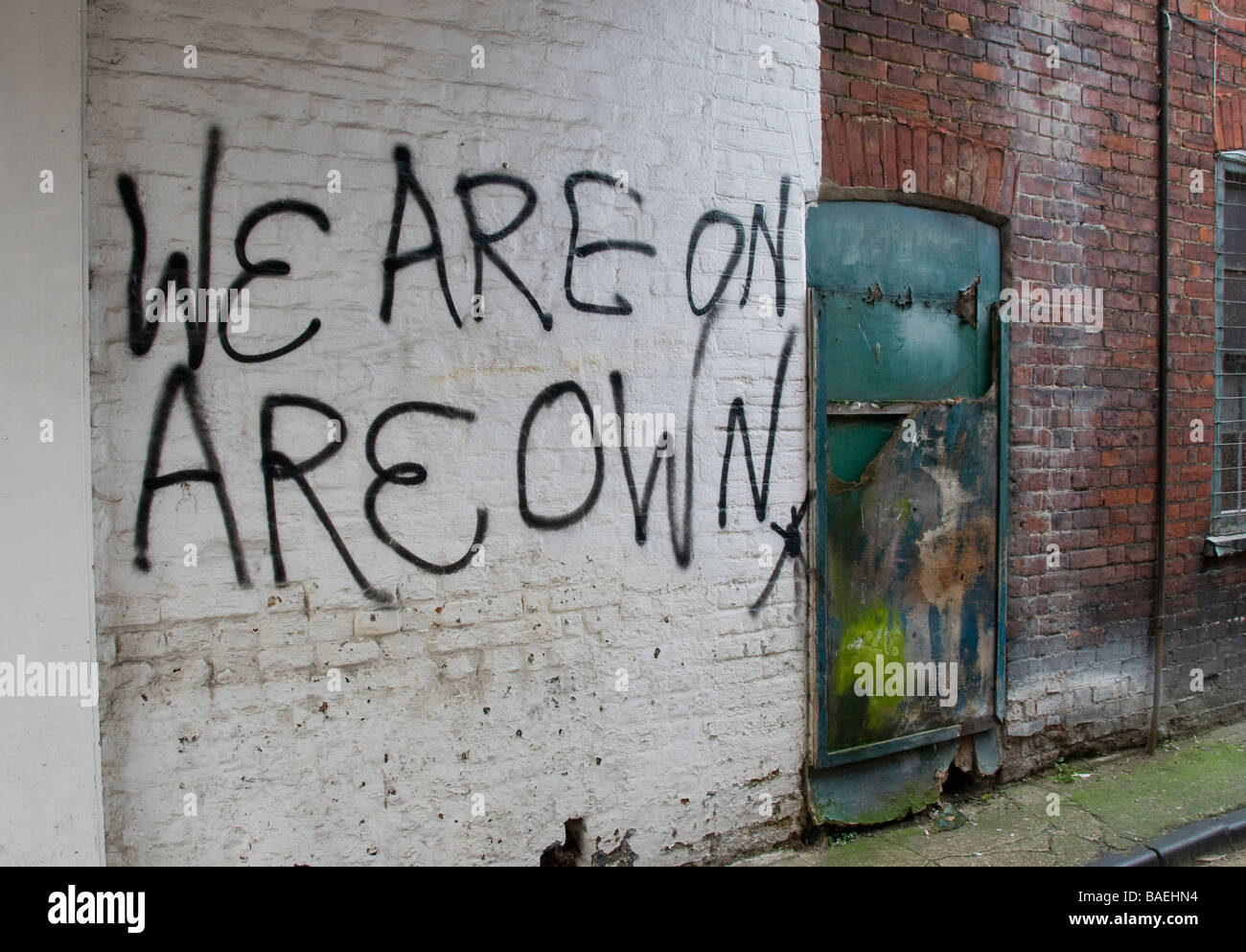 Graffiti on white brick wall in a run down area, stating 'we are on Stock  Photo - Alamy