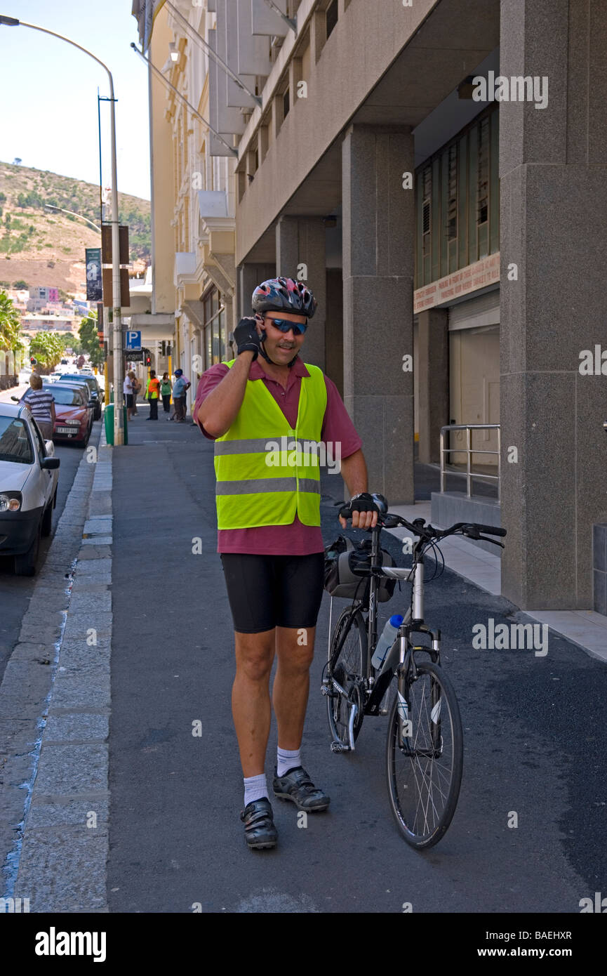 Bicyclist making a call on his mobile phone Cape Town South Africa - Stock Image