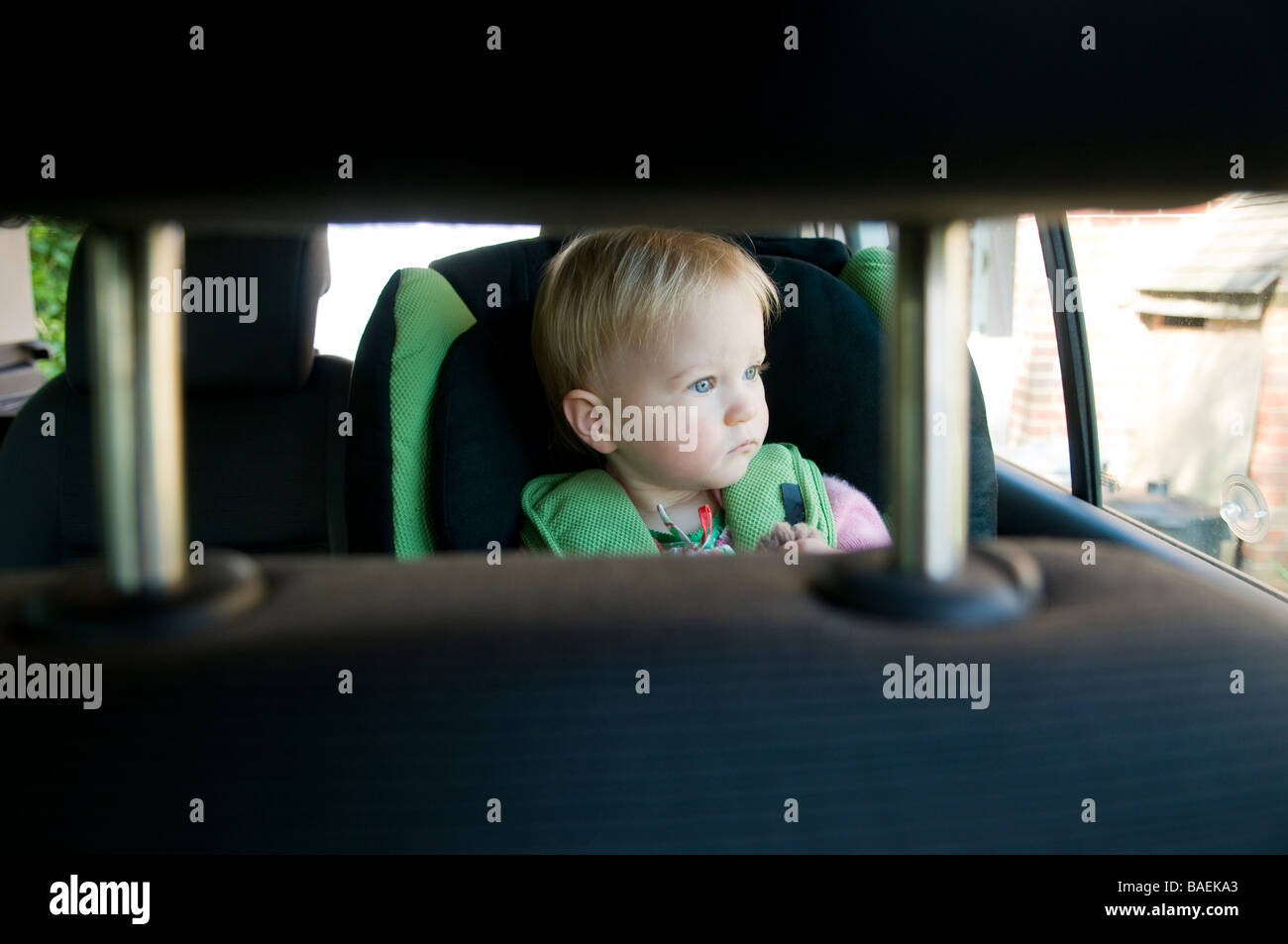 BABY GIRL CHILD IN CAR SEAT LOOKING OUT OF THE REAR WINDOW - Stock Image