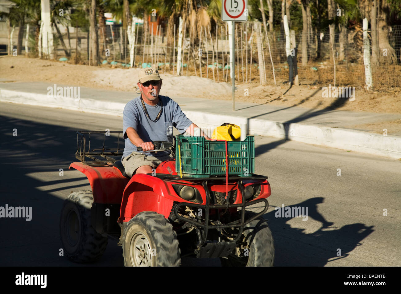 MEXICO Los Barriles Retired American man driving ATV on street in town and smoking cigar - Stock Image