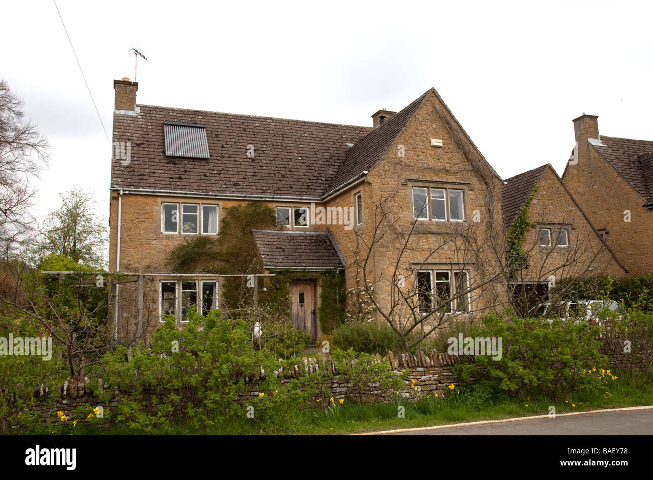 Solar thermal evacuated tubes to heat water on tile roof of large Cotswold house UK - Stock Image