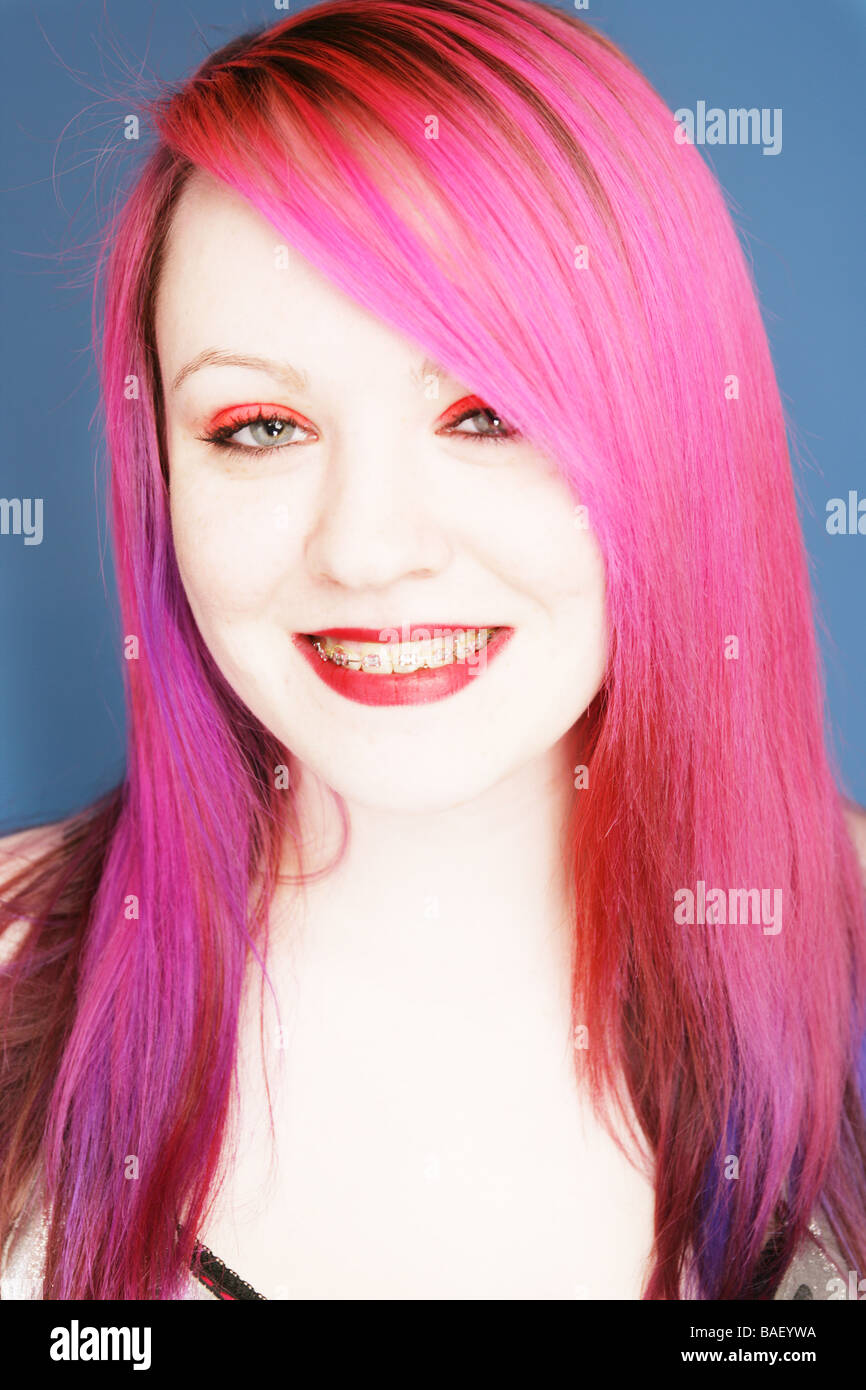 Young teen goth with bright pink hair wearing braces smiling at camera.