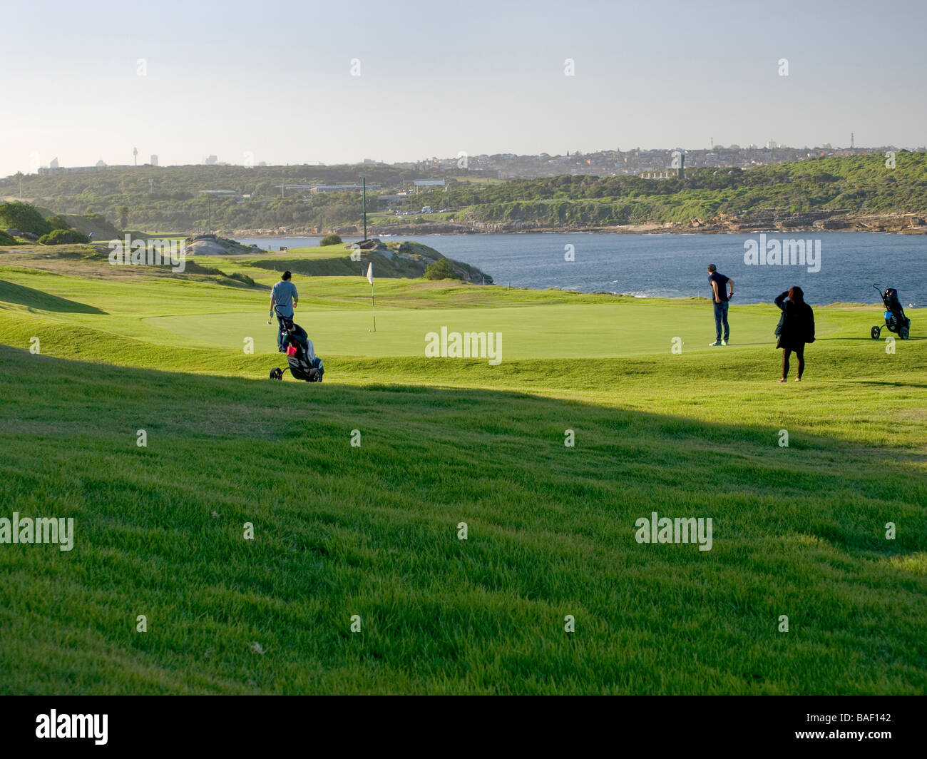 Golfers on green about to putt - Stock Image