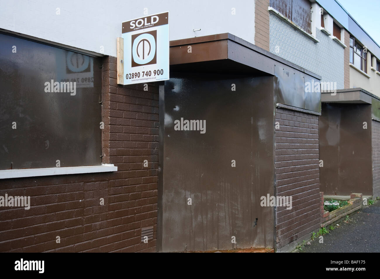 Boarded up houses with 'Sold' estate agent sign. - Stock Image