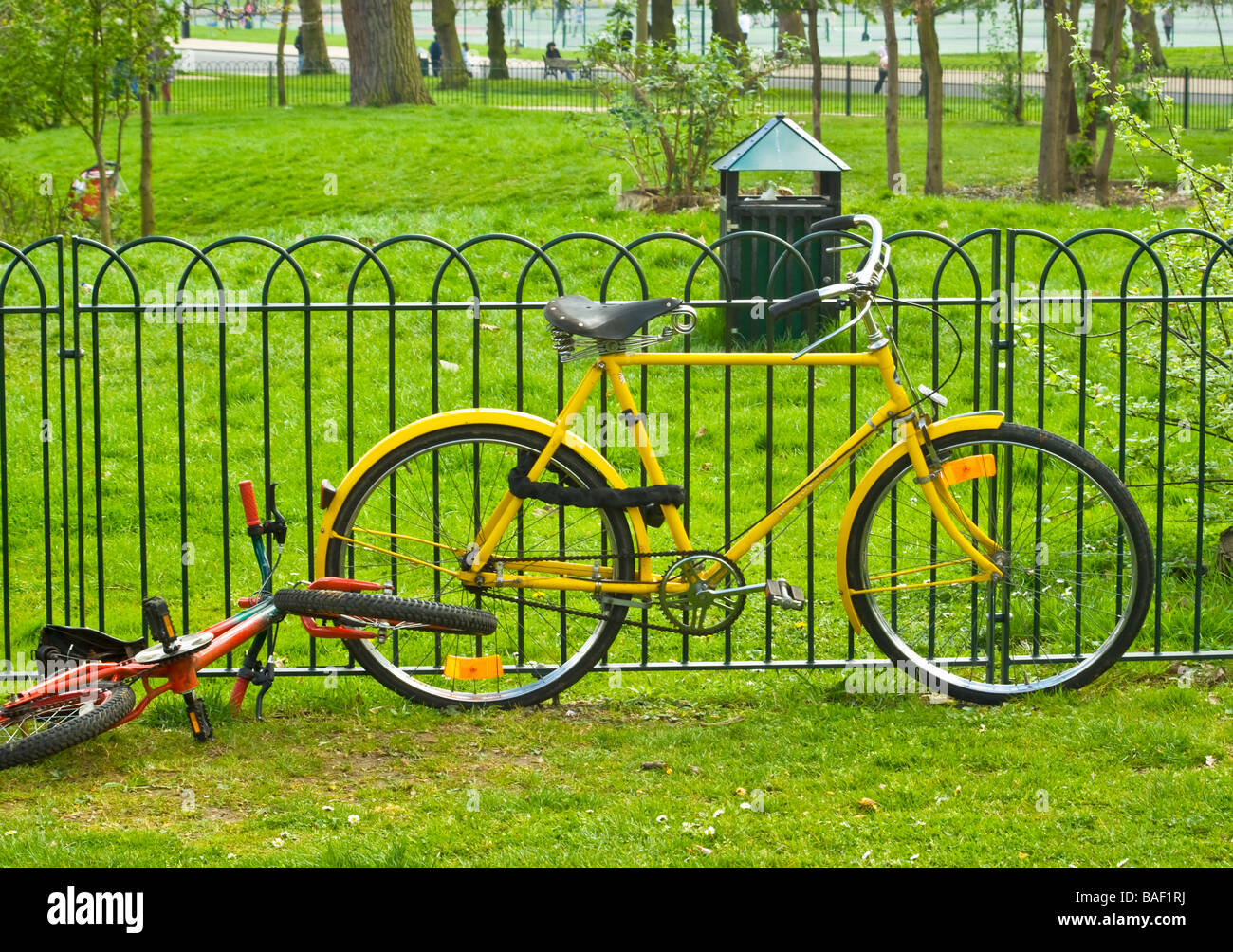 Unusual classically styled yellow gents cycle chained to park railings. A red and green child's cycle thrown - Stock Image