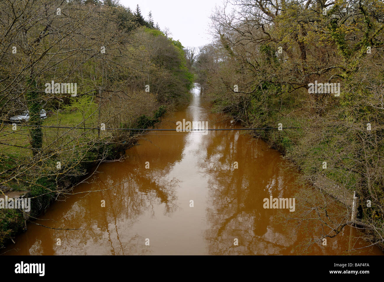 River Teign turns red due to pollution from a nearby quarry South Devon England - Stock Image