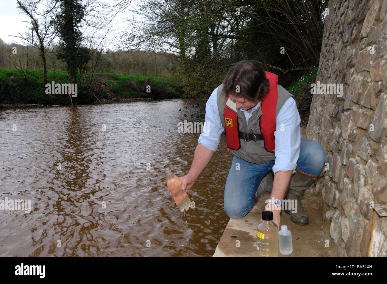 Environment Agency officer takes water sample from polluted river Teign after incident at nearby quarry South Devon - Stock Image
