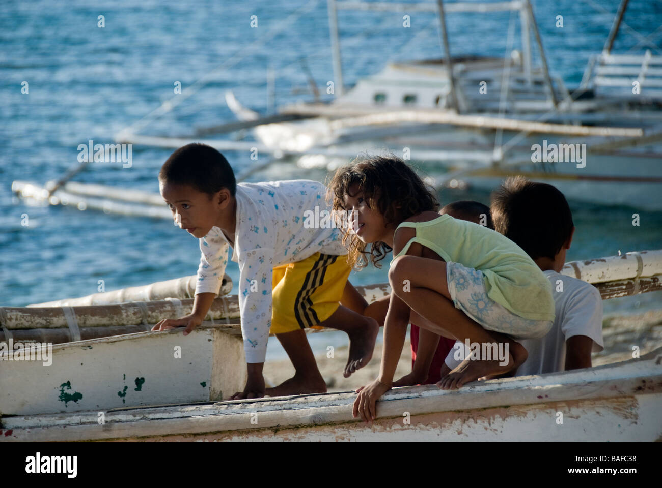 Children playing in a boat on the beach at Apo Island, Philippines Stock Photo