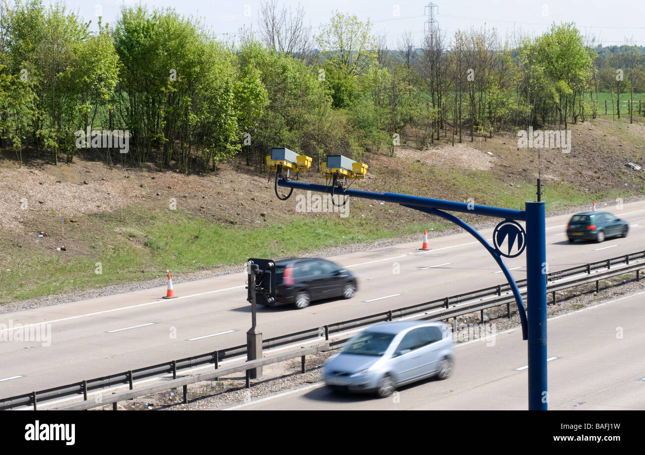 M25 Traffic passes below Surveillance cameras as it travels through Essex, England. - Stock Image