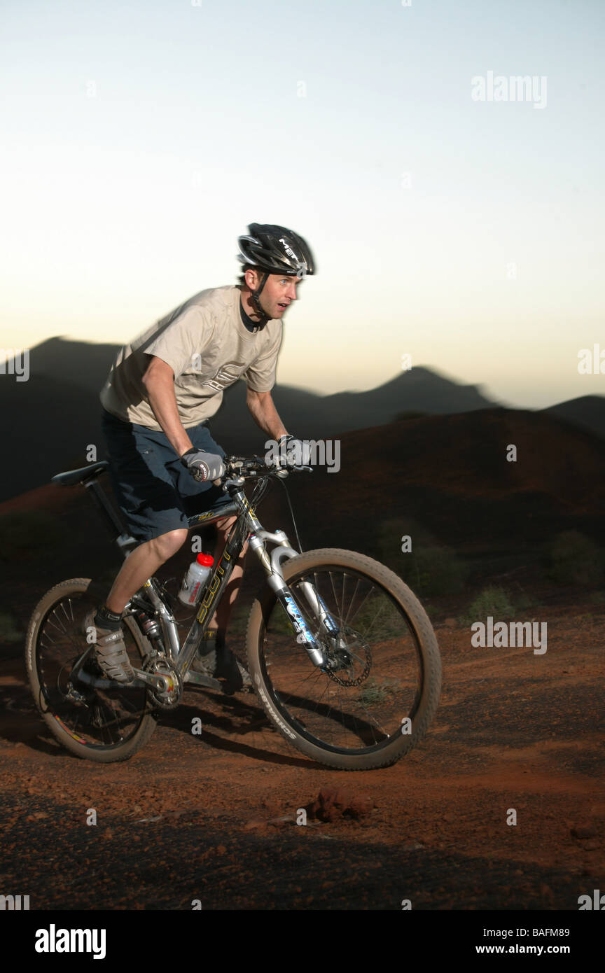 A Mountain biker riding his MTB in the mountains. - Stock Image