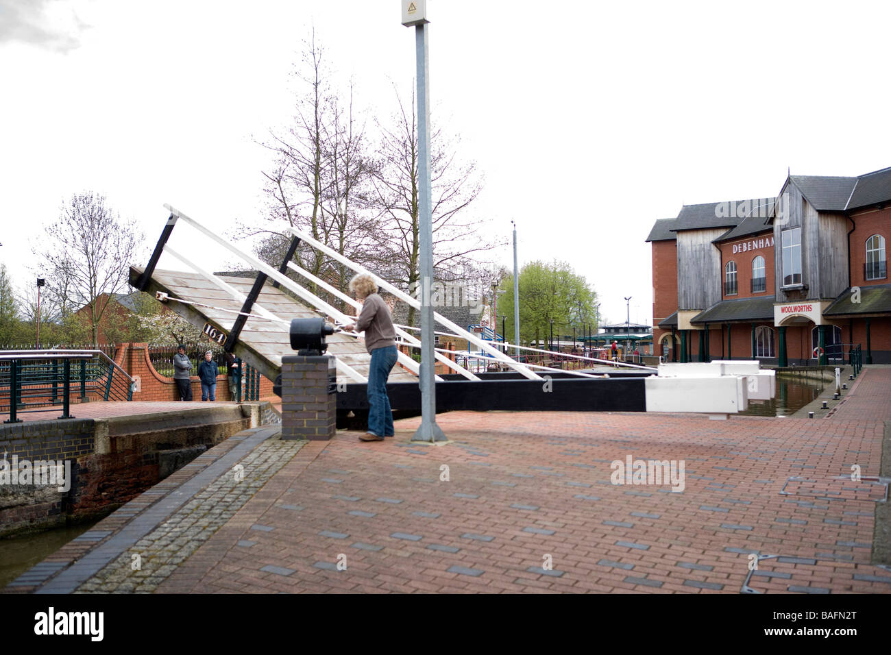 A lift bridge being wound up manually with a windlass on the Oxford canal in the town of Banbury - Stock Image