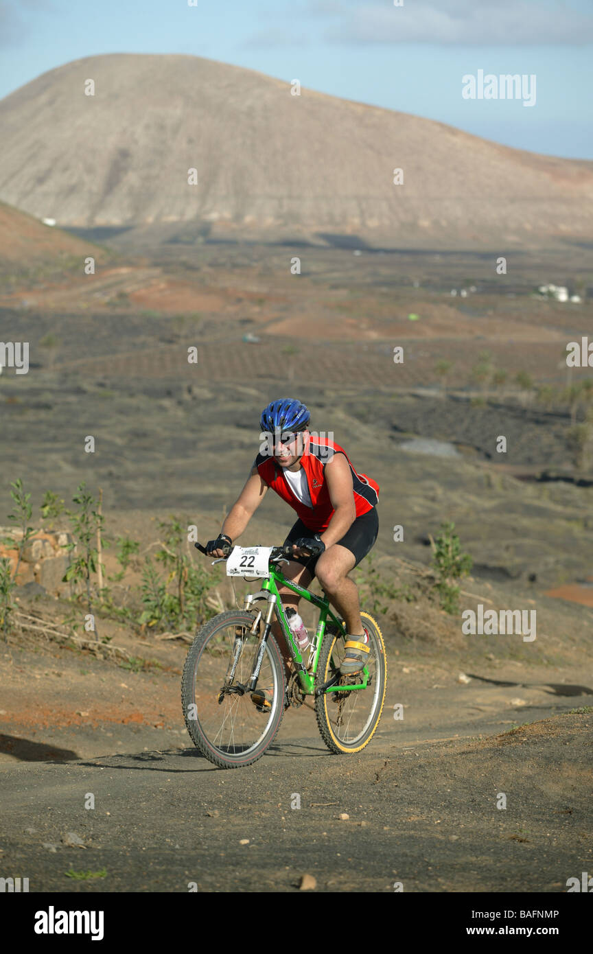 A Mountain biker racing his MTB in rocky terrain. - Stock Image