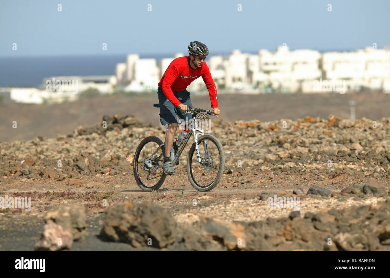A Mountain biker riding his MTB in rocky terrain. - Stock Image