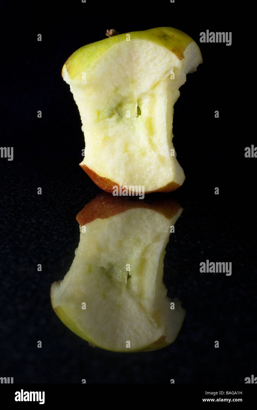 Core of a braeburn apple on a polished black granite surface - Stock Image