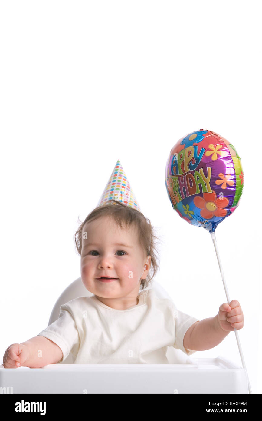 Toddler with party-hat and Happy Birthday balloon - Stock Image