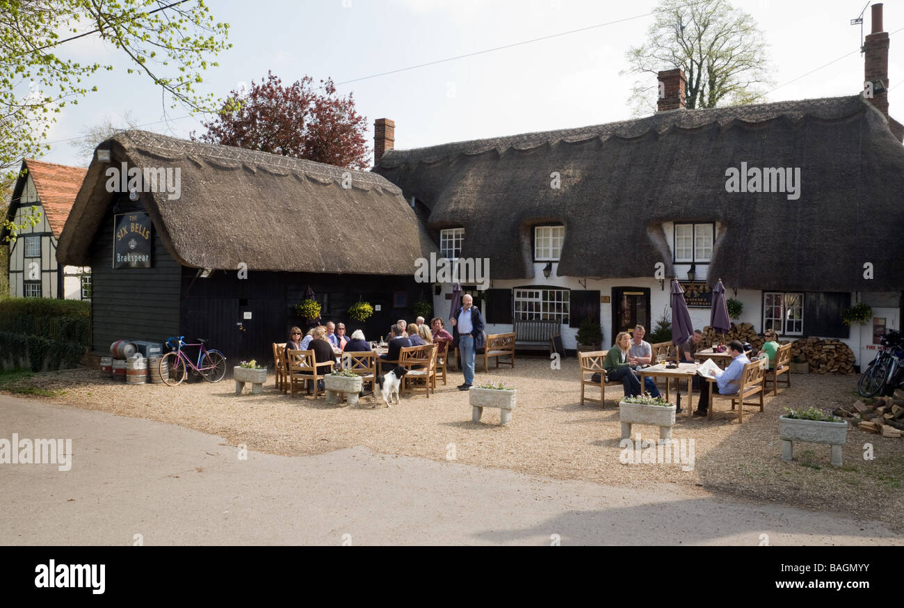People sitting drinking outside the Six Bells on the Green pub in Warborough, Oxfordshire - Stock Image