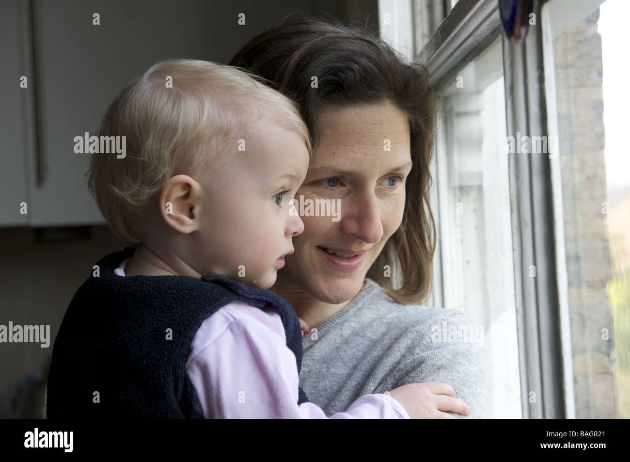 Mother and one year old daughter looking out of a window - Stock Image
