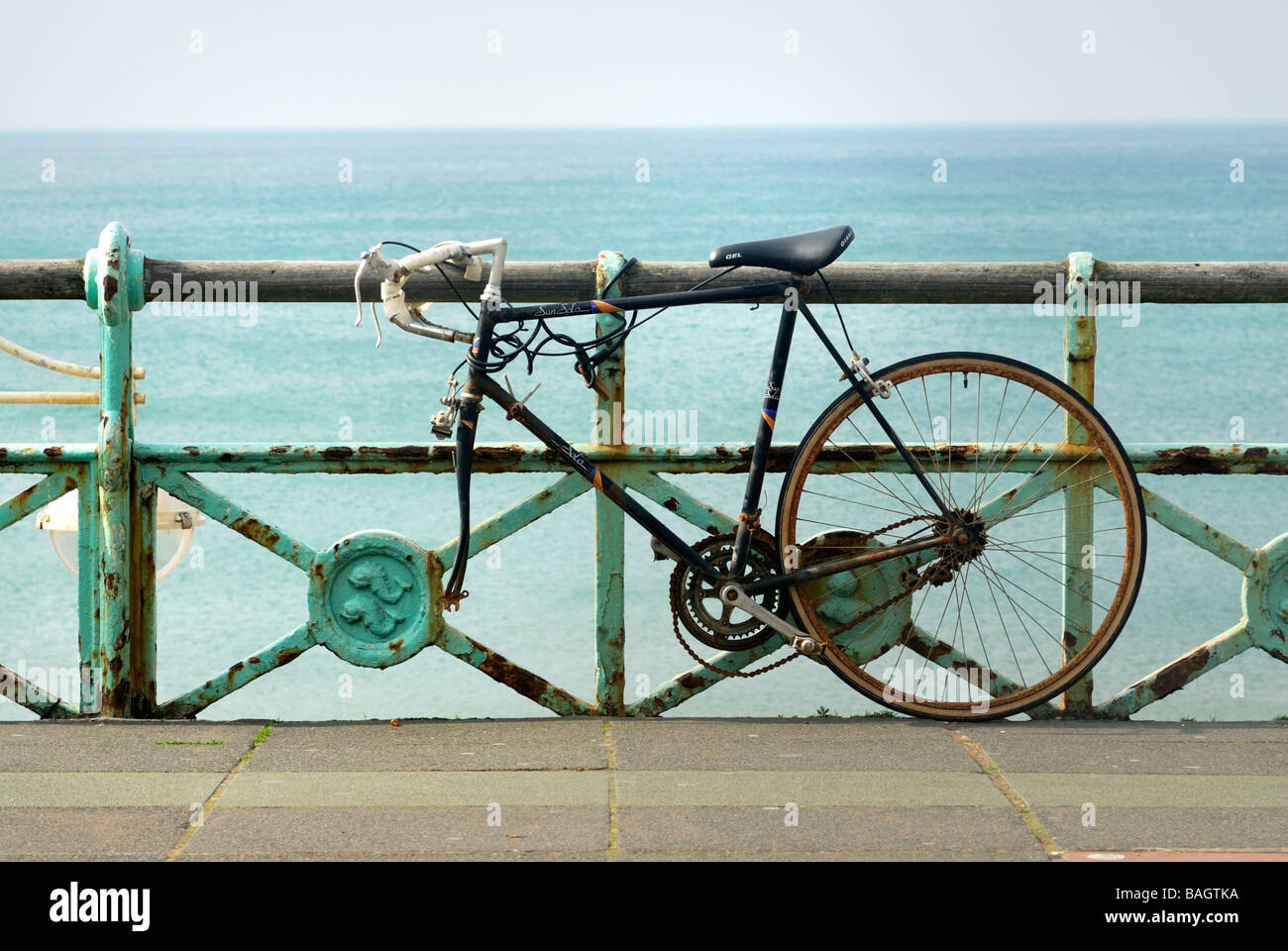 Old bicycle chained to railings on Brighton Seafront - Stock Image