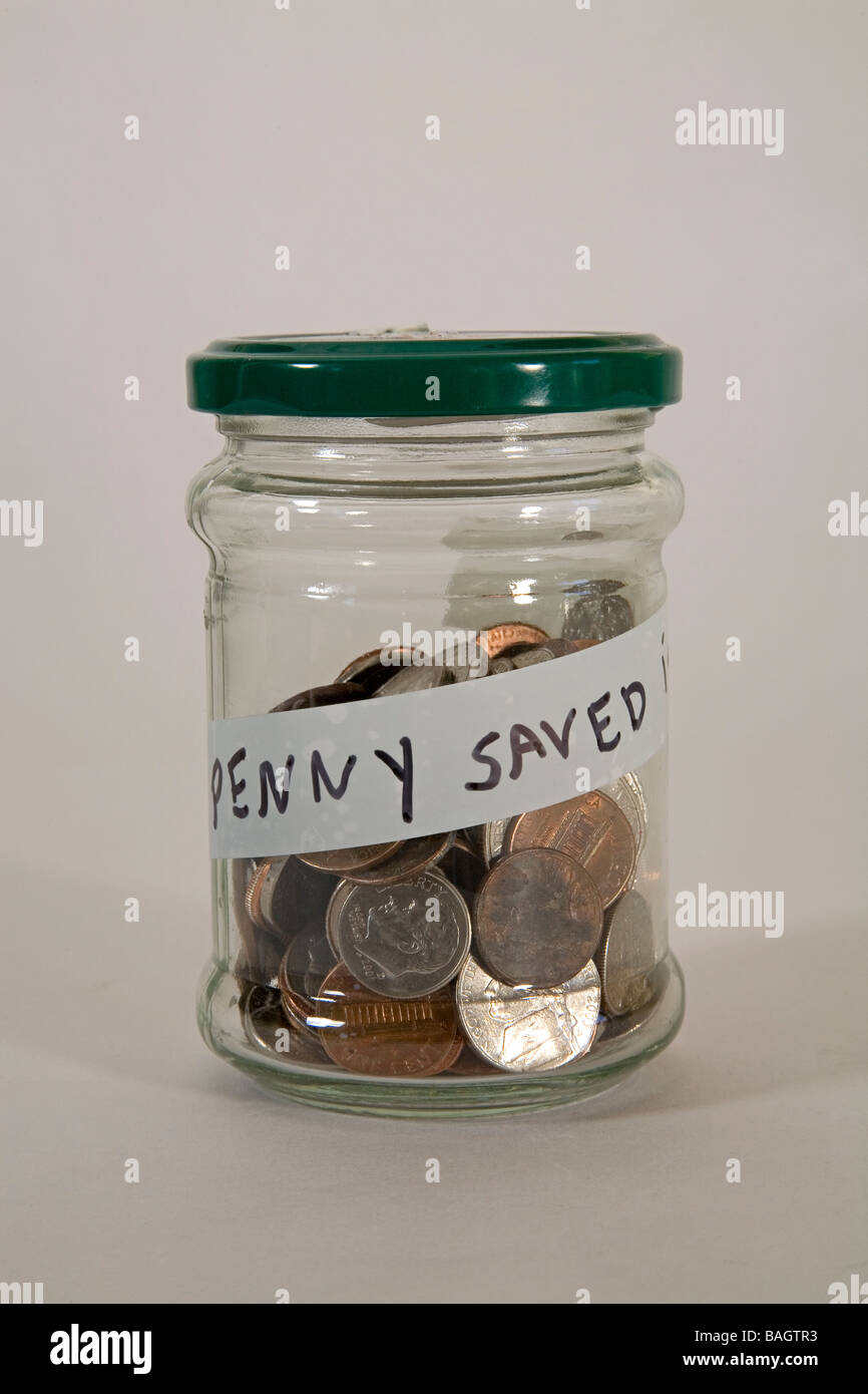A jar filled with coins, a penny saved is a penny earned. - Stock Image