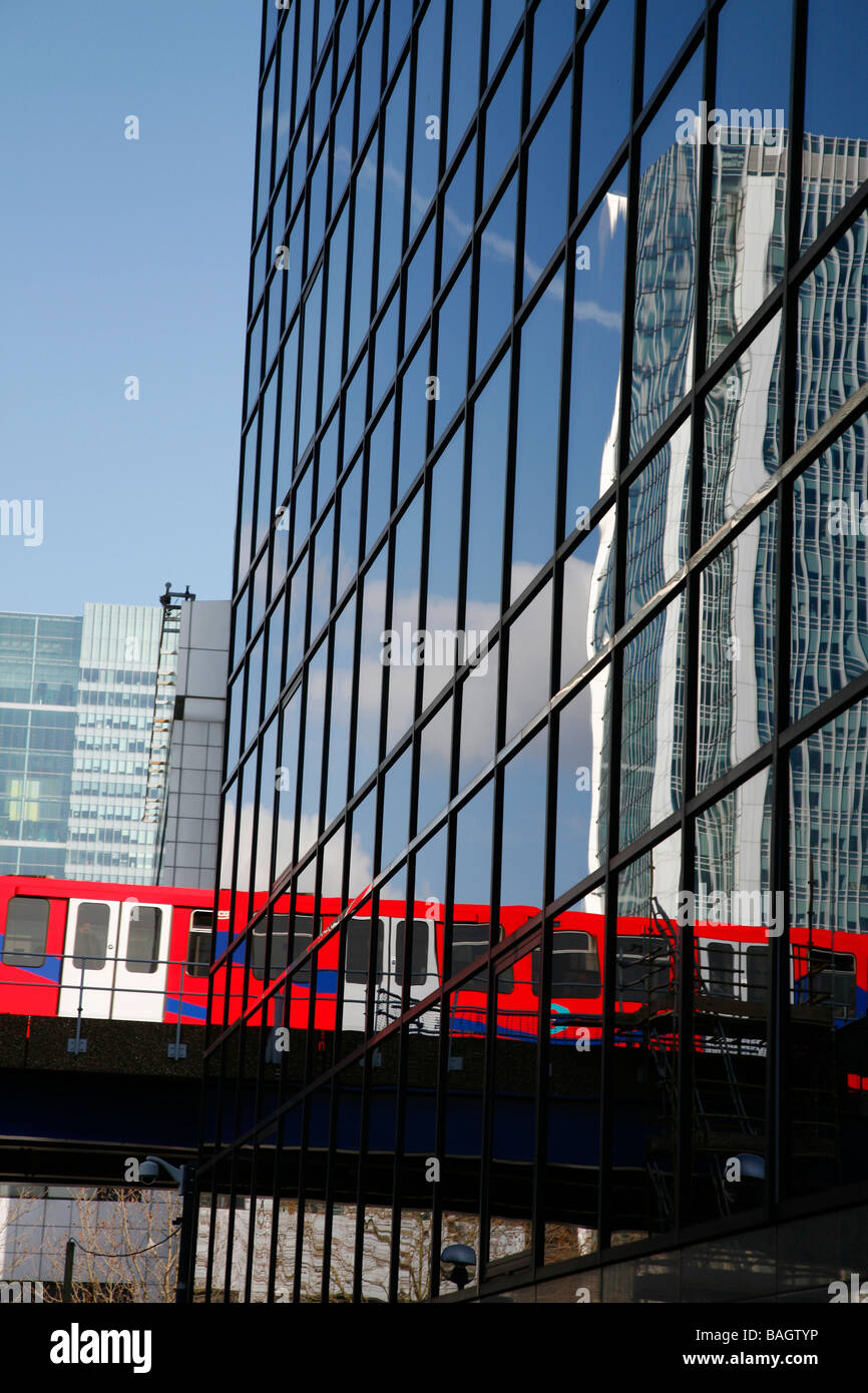 DLR train reflected in offices by Millwall Outer Dock, Isle of Dogs, London, UK - Stock Image
