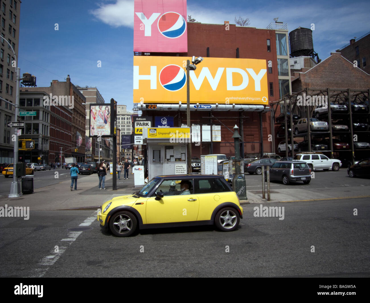 A Mini Cooper in front of an advertisement for Pepsi Cola in the New York neighborhood of NoHo - Stock Image