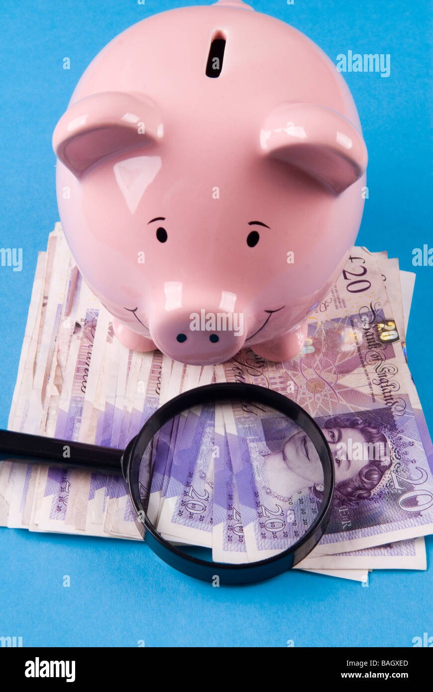 Piggy bank with magnifying lens over British money - Stock Image