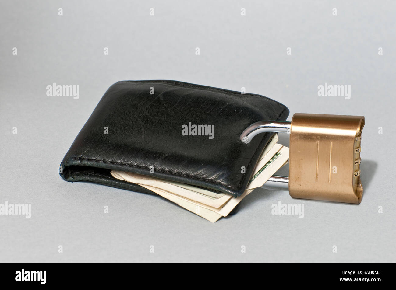 Wallet with lock representing shoppers economizing and being tightfisted with their money - Stock Image