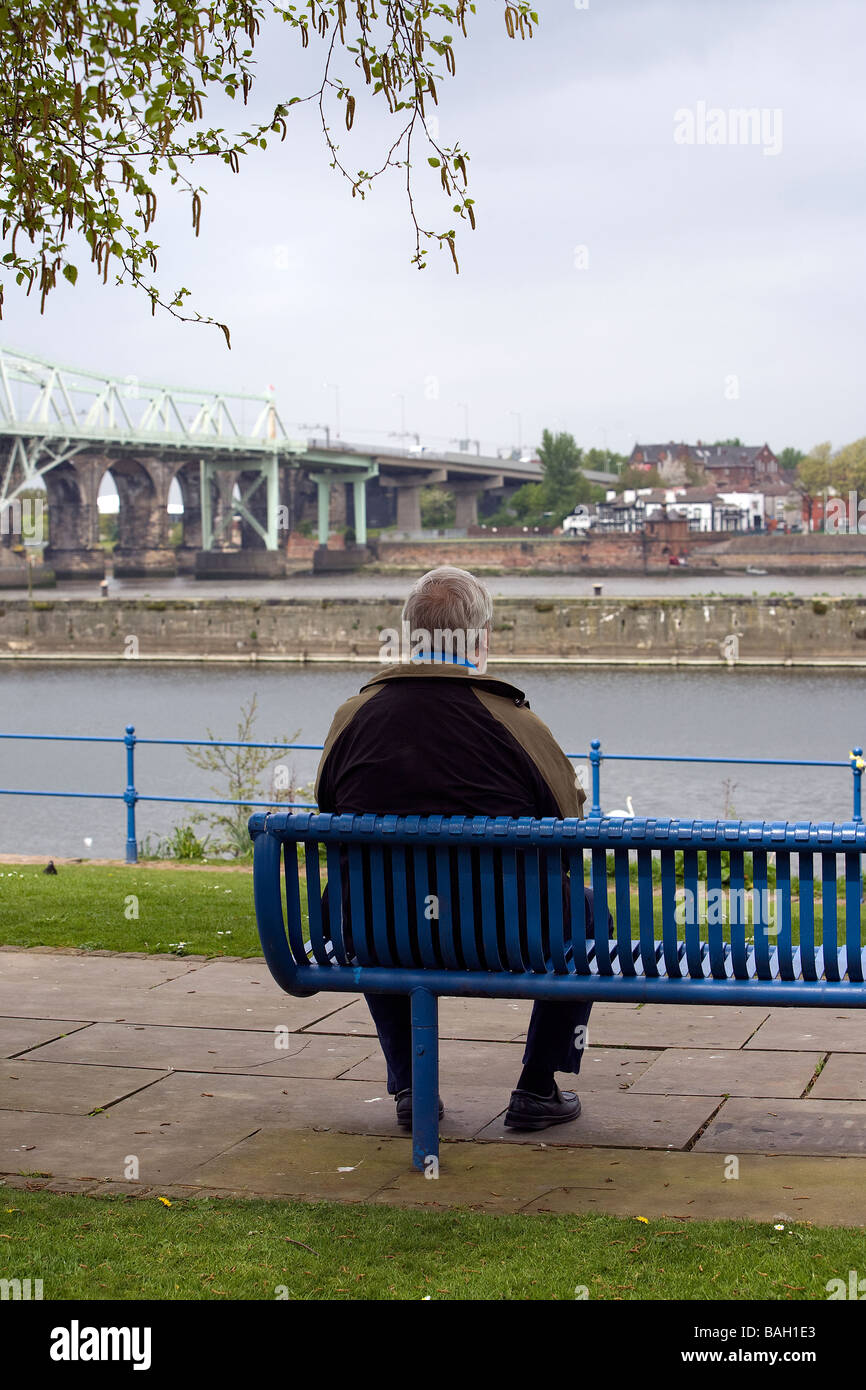 A solitary man sits on a blue seat looking toward the Silver Jubilee Bridge over the River Mersey and Manchester - Stock Image