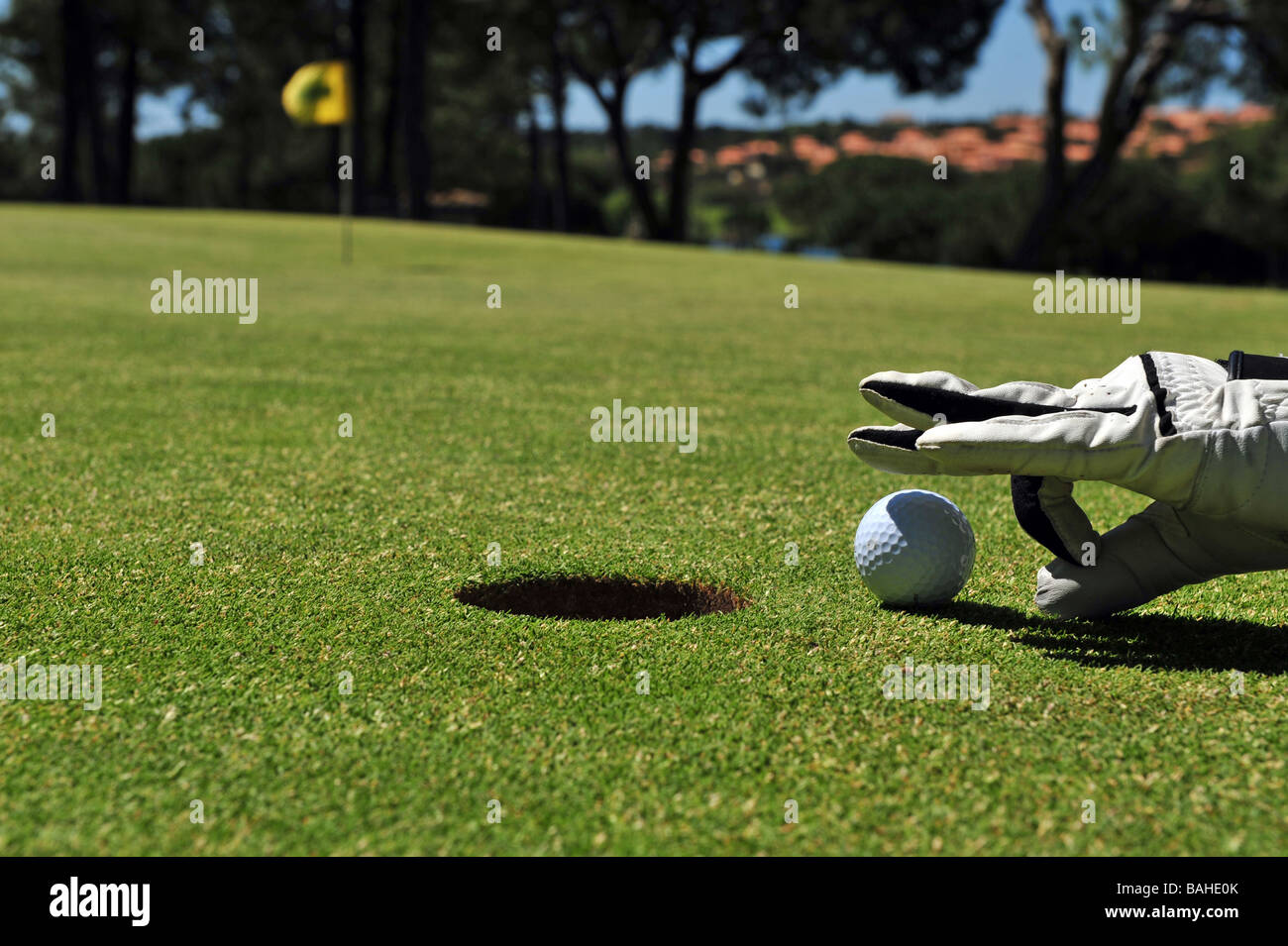 Flicking a golf ball into the hole - Stock Image