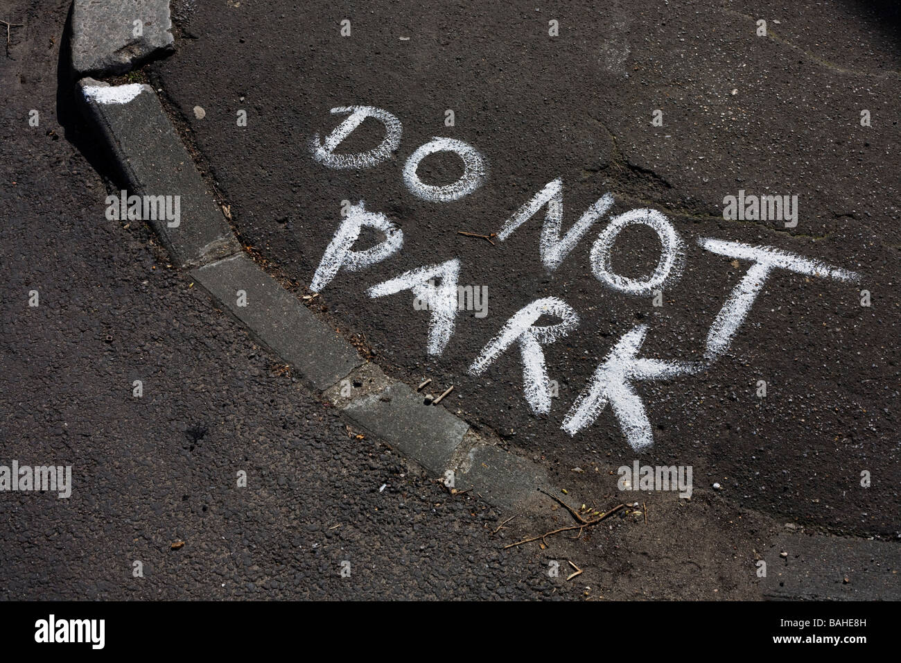 The words Do Not Park have been painted roughly on a kerbside street corner in the London borough of Lambeth England - Stock Image