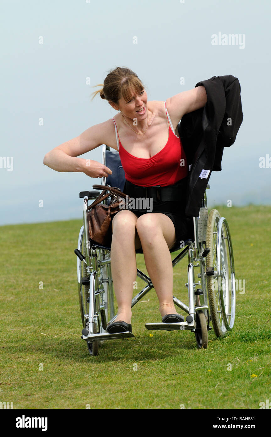 Disabled woman wheelchair user removing her jacket - Stock Image