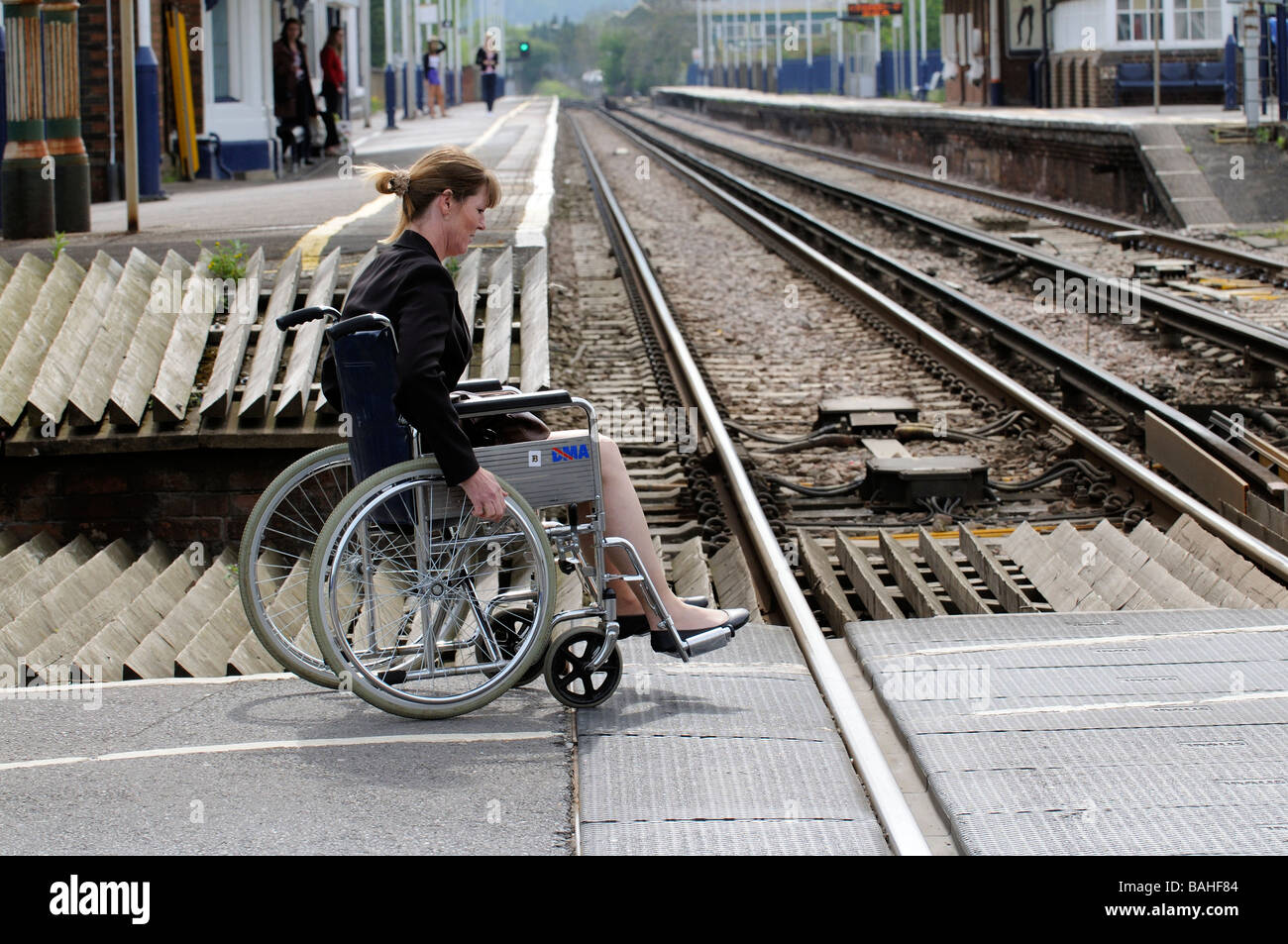 Woman in a wheelchair crossing railway line to reach the platform England UK - Stock Image