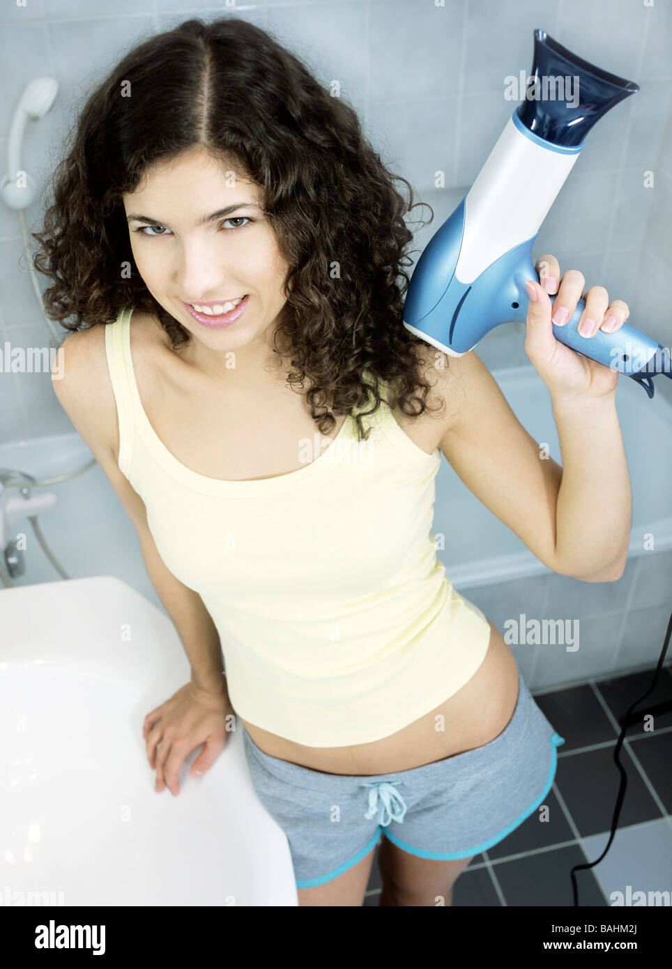 people, woman, girl, teenager, 15-20, 20-25, dark, haired, smile, smiling, curly, hairdrier, indoor, bathroom, vertical - Stock Image