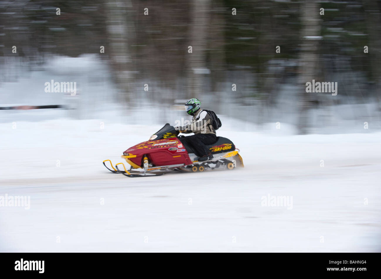 A SNOWMOBILE IN MOTION DRIVES ON A TRAIL THROUGH THE PORCUPINE MOUNTAINS STATE PARK - Stock Image