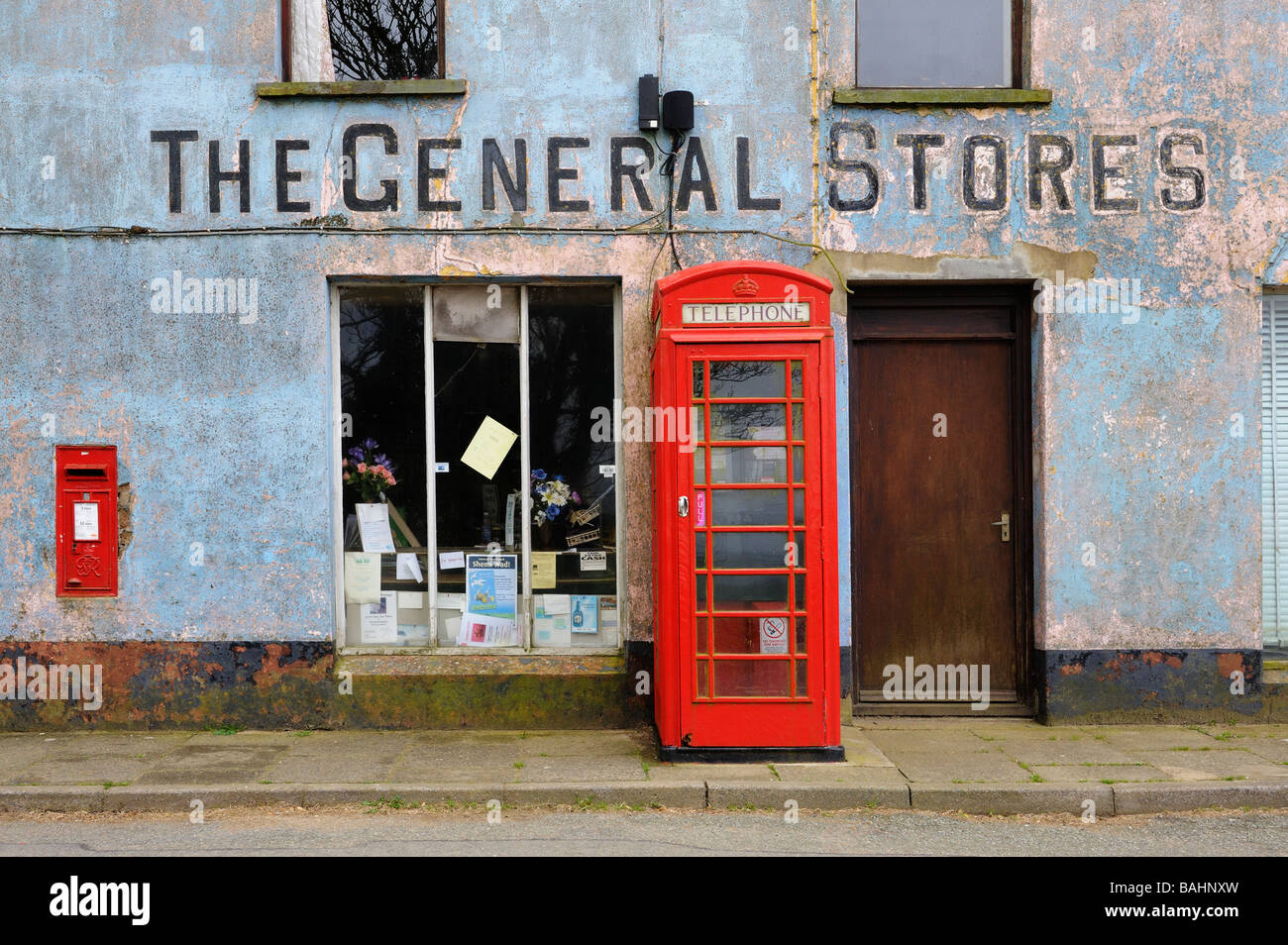 A red telephone box outside a derelict General Stores in Mathri Pembroke Wales Stock Photo