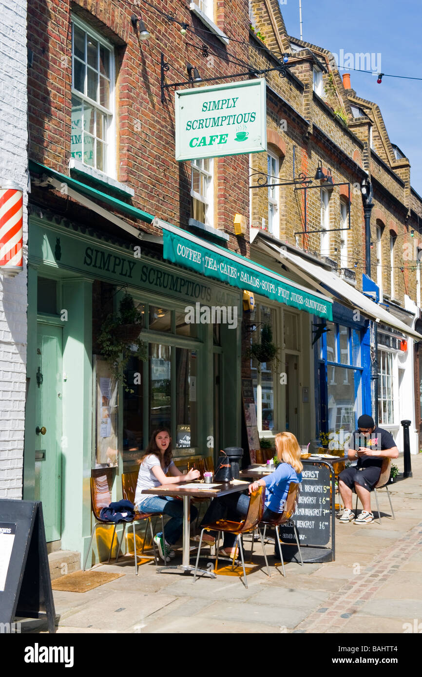 Spring in Hampstead Village , The Simply Scrumptious cafe in Flask Walk customers sitting outside enjoying the sun - Stock Image
