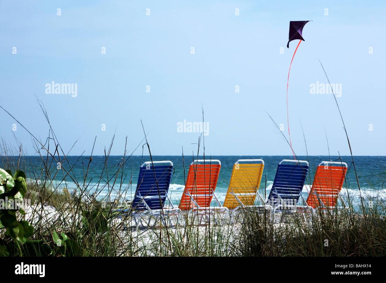 Bradenton Beach, Florida, USA; Beach chairs lined on beach and a kite flying - Stock Image