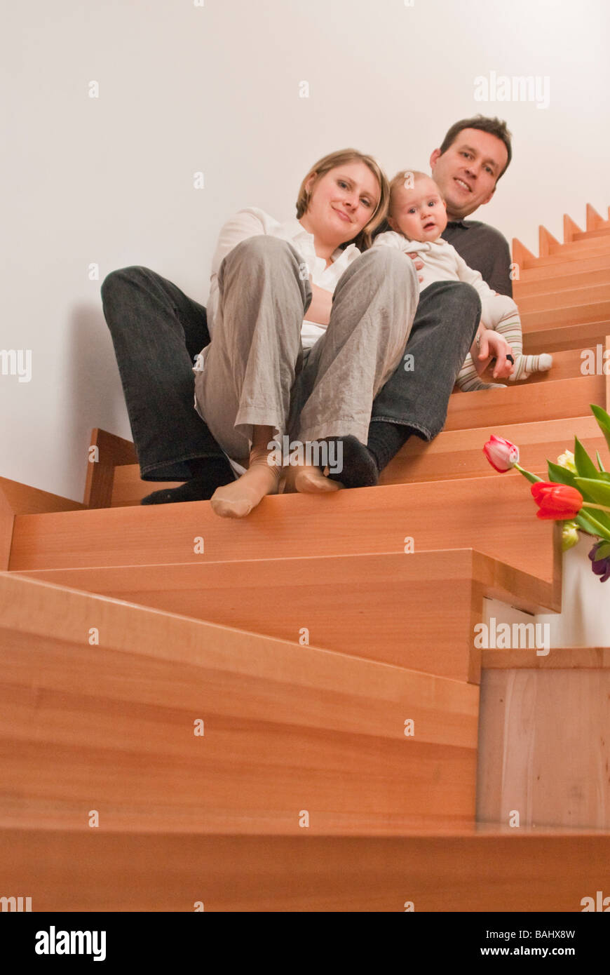 Family sitting on a staircase - Stock Image