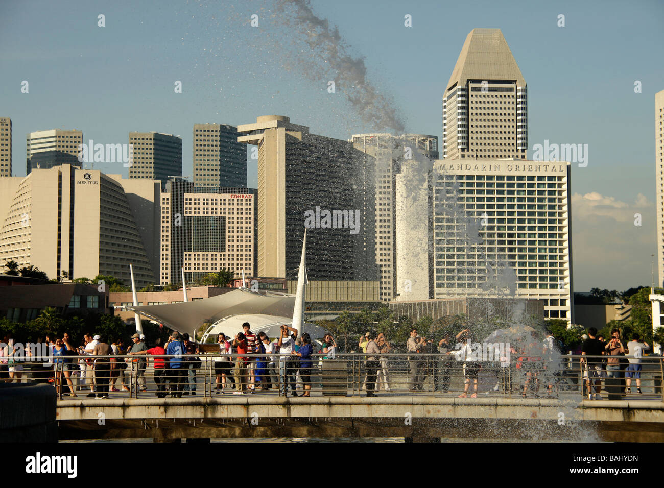 tourists watching the Merlion fountain in Singapore Asia - Stock Image