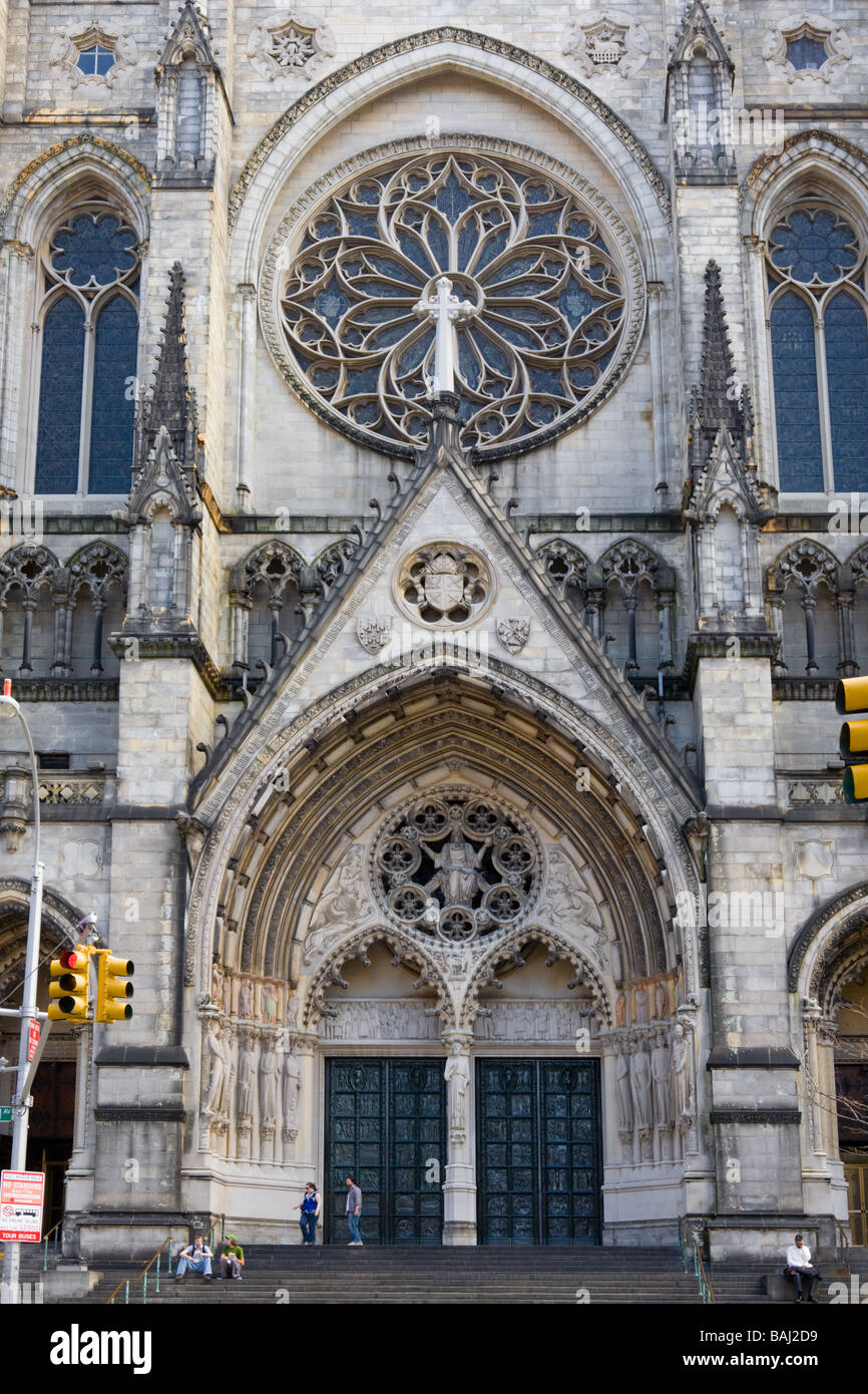 Main entrance door dwarfs tourists Cathedral of Saint John the Divine New York City - Stock Image