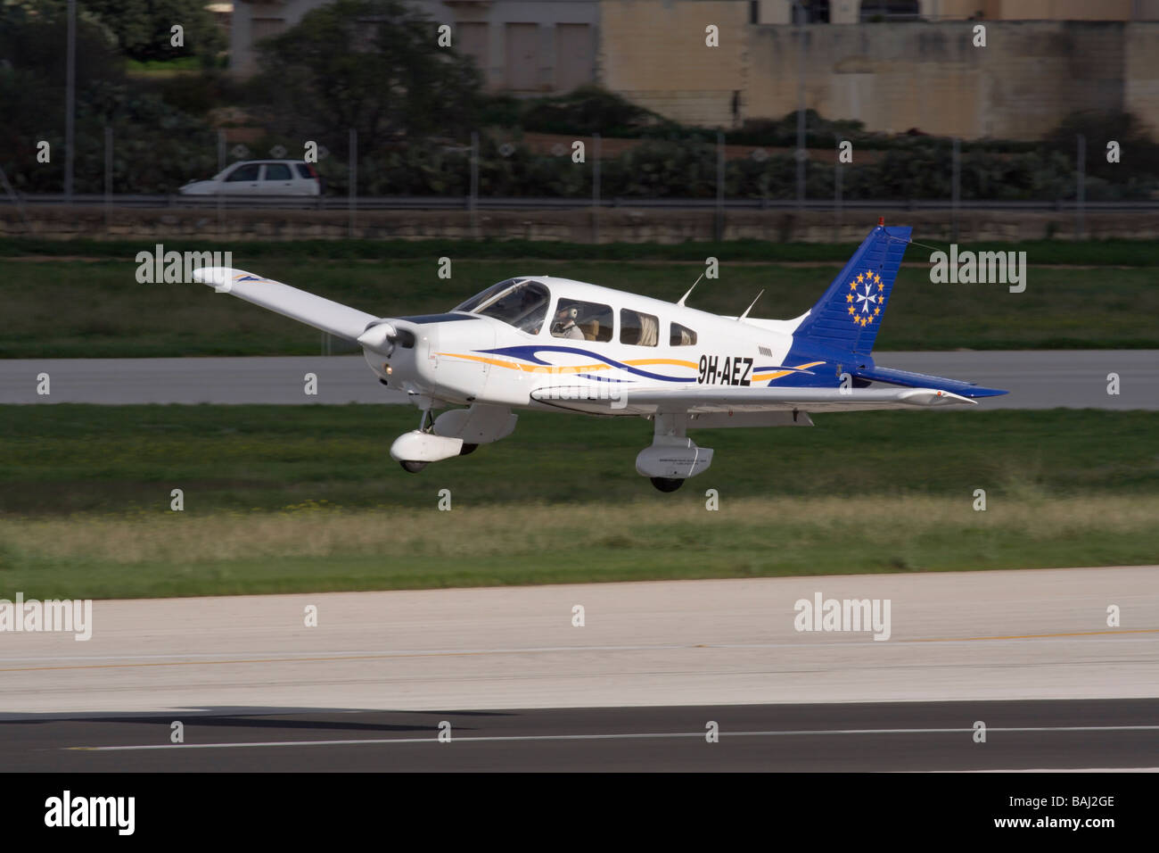 Piper PA-28 Warrior II single-engine light private plane flying low over the runway - Stock Image