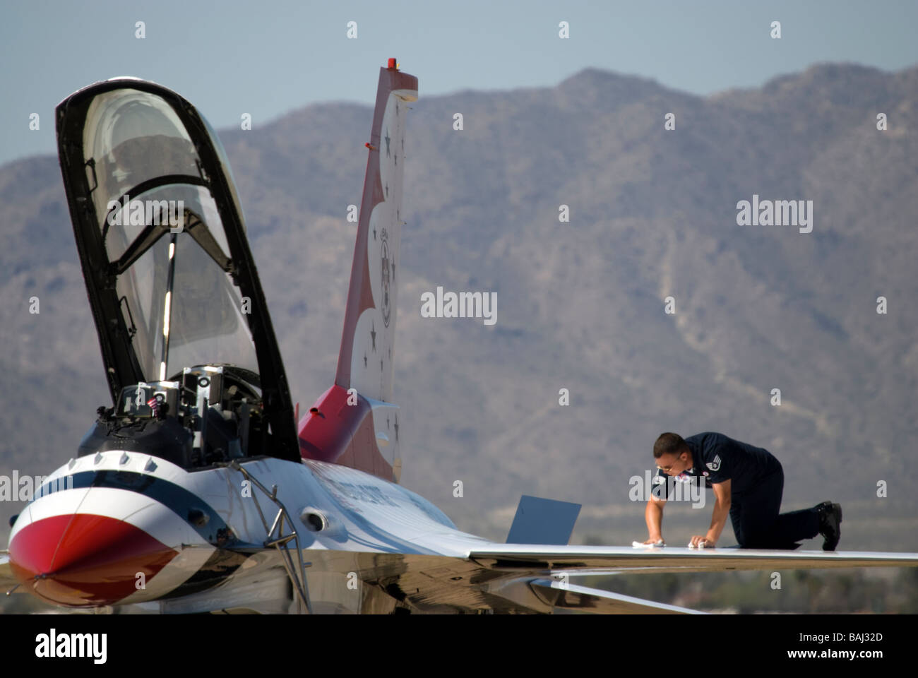 A crew member works on the wing of an F-16 'Thunderbird' before a demonstration at an airshow. - Stock Image