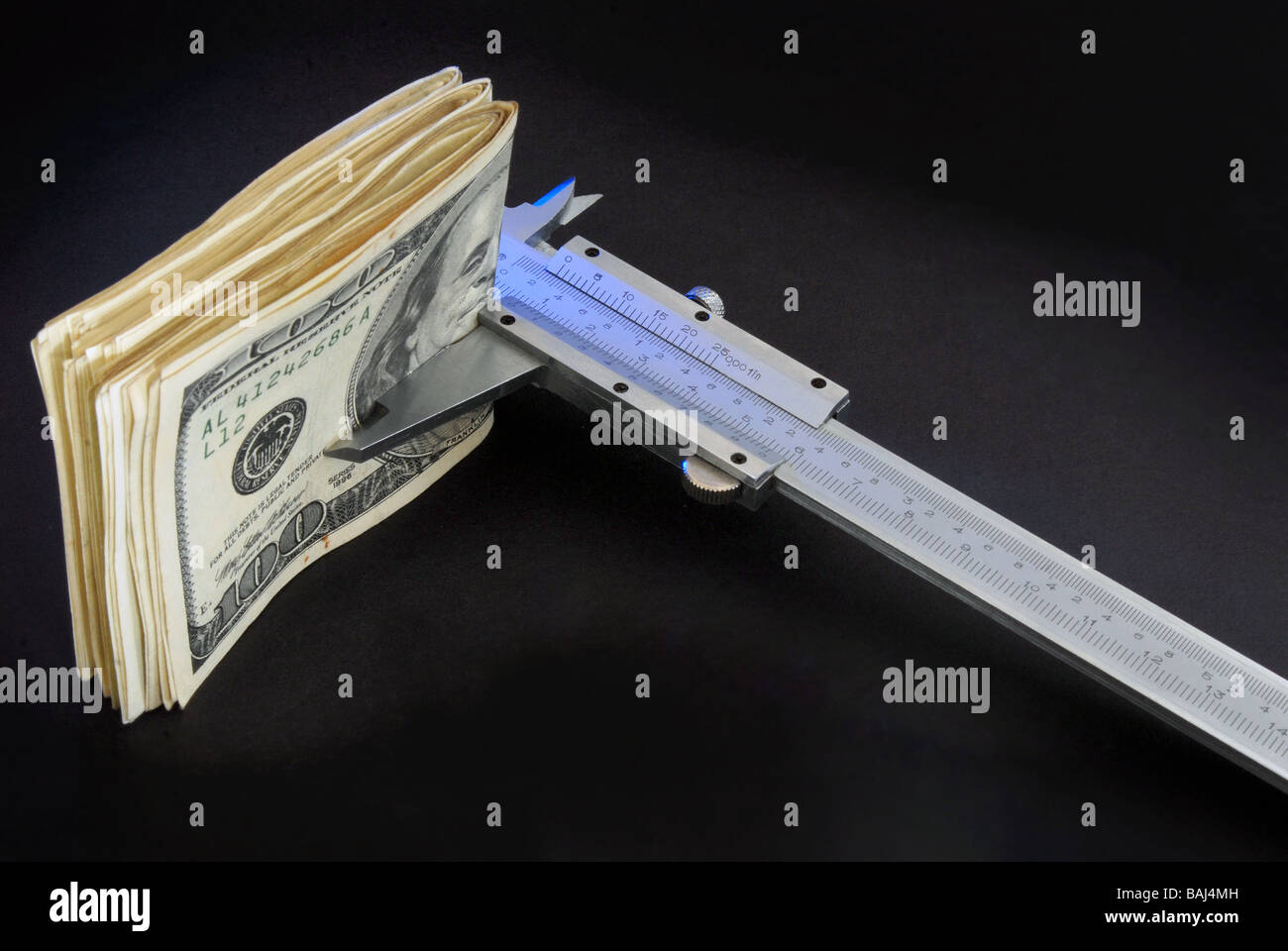 Close up of a pile of one hundred dollar bill been measured for a caliber - Stock Image